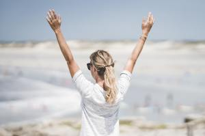 confident women with arms up, facing the other side
